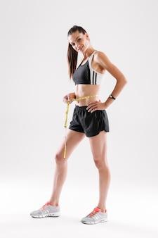 Retrato de corpo inteiro de uma desportista feliz sorridente
