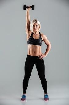 Retrato de corpo inteiro de uma desportista muscular concentrada