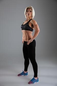 Retrato de corpo inteiro de uma desportista muscular motivada e adulta