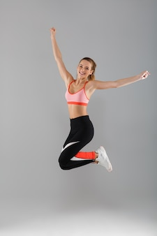 Retrato de corpo inteiro de uma desportista sorridente feliz comemorando