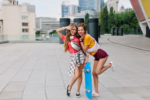 Retrato de corpo inteiro de uma divertida garota engraçada andando de pé em uma perna com um skate azul ao lado do melhor amigo