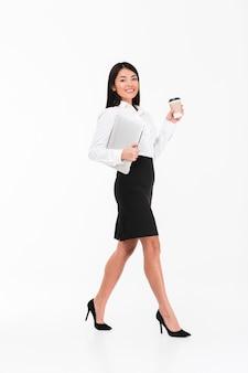 Retrato de corpo inteiro de uma empresária asiática feliz andando