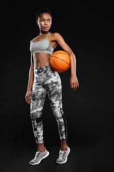 Retrato de corpo inteiro de uma esportista segurando uma bola de basquete isolada em uma parede preta