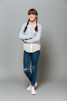 Retrato de corpo inteiro de uma estudante bonita sorridente