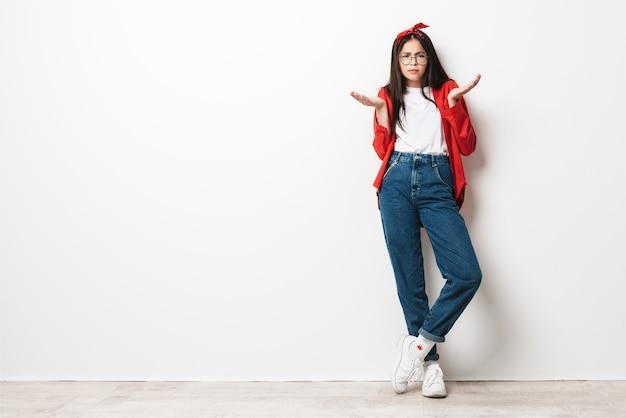 Retrato de corpo inteiro de uma fofa adolescente confusa, vestindo roupa casual, isolada sobre uma parede branca, encolhendo os ombros
