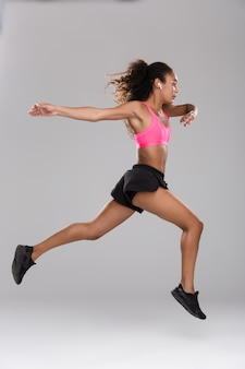 Retrato de corpo inteiro de uma forte jovem desportista africana fazendo exercícios isolados sobre um fundo cinza, aquecendo, pulando