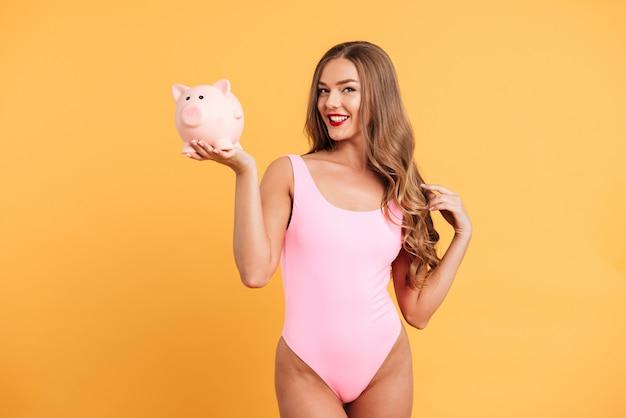 Retrato de corpo inteiro de uma garota atraente feliz em traje de banho