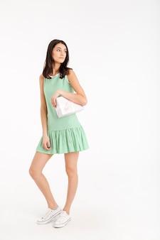 Retrato de corpo inteiro de uma garota bonita, vestida de vestido