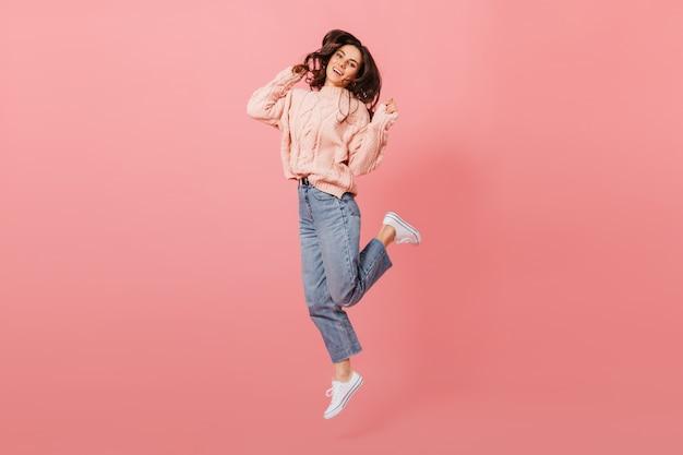 Retrato de corpo inteiro de uma garota de cabelos escuros pulante. senhora de jeans e suéter rosa, se divertindo no fundo isolado.