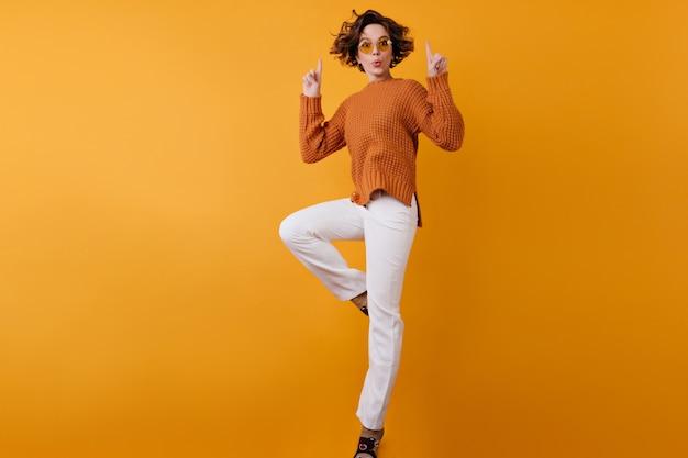 Retrato de corpo inteiro de uma garota despreocupada em calças brancas pulando no espaço laranja