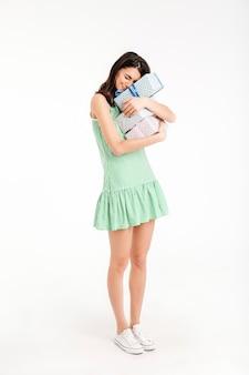 Retrato de corpo inteiro de uma garota encantada, vestida de vestido