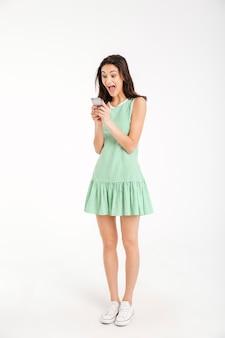 Retrato de corpo inteiro de uma garota excitada no vestido