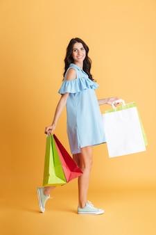 Retrato de corpo inteiro de uma garota feliz andando com sacolas de compras isoladas