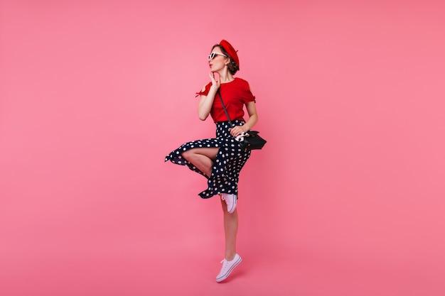 Retrato de corpo inteiro de uma garota magra atraente. maravilhosa modelo feminina de boina e saia dançando.