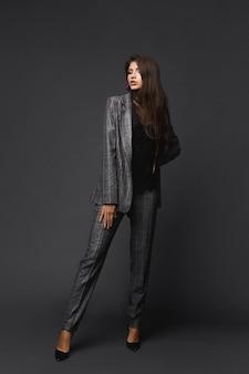 Retrato de corpo inteiro de uma garota modelo confiante em um terno xadrez moderno no fundo cinza, conceito de moda empresarial