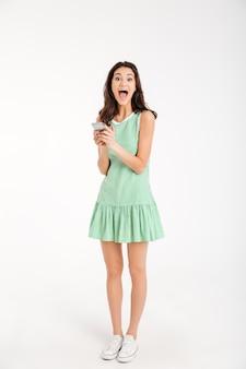 Retrato de corpo inteiro de uma garota surpresa no vestido