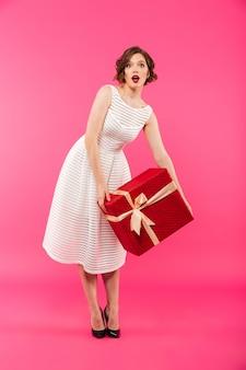 Retrato de corpo inteiro de uma garota surpresa, vestida de vestido