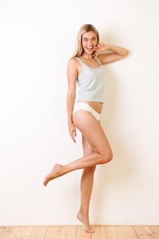 Retrato de corpo inteiro de uma jovem alegre em roupa interior