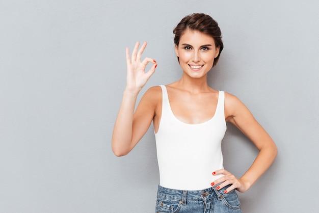 Retrato de corpo inteiro de uma jovem alegre, mostrando sinal de ok com os dedos isolados no fundo cinza
