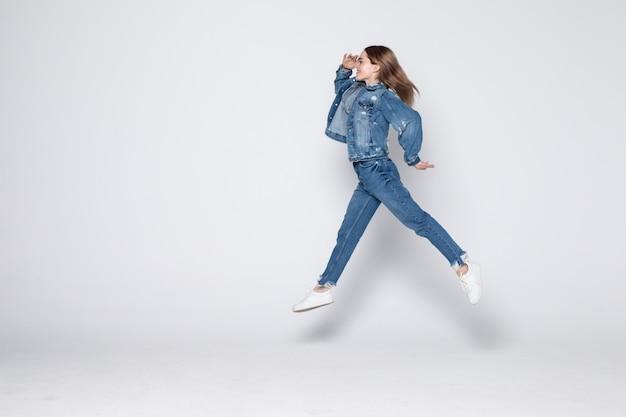 Retrato de corpo inteiro de uma jovem alegre, pulando e comemorando por cima da parede cinza