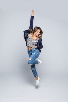 Retrato de corpo inteiro de uma jovem alegre pulando e comemorando sobre uma parede cinza