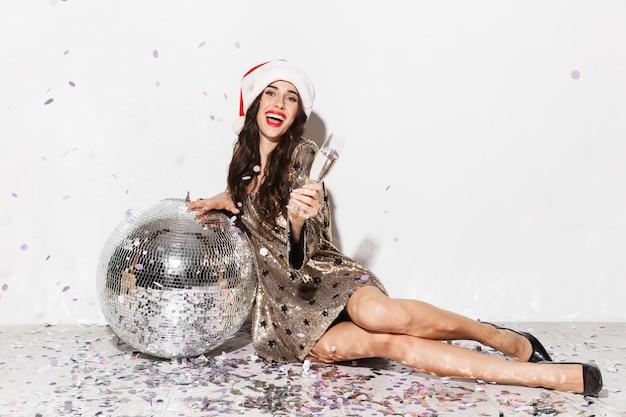 Retrato de corpo inteiro de uma jovem animada com chapéu vermelho comemorando o ano novo isolado no branco, sentado com uma bola de discoteca prateada, segurando uma taça de champanhe