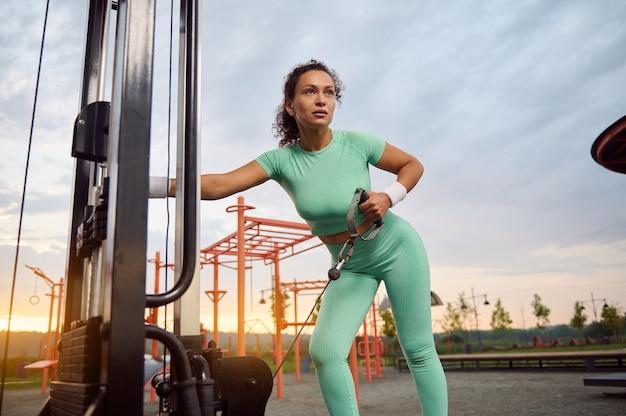 Retrato de corpo inteiro de uma jovem atlética, de nacionalidade mista, realizando levantamento terra com flexão para frente em uma máquina de ginástica ao ar livre