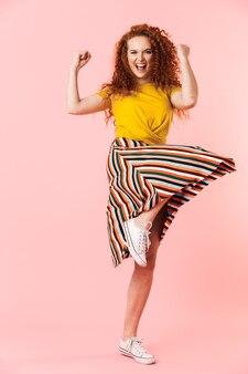 Retrato de corpo inteiro de uma jovem atraente com cabelo ruivo encaracolado comprido pulando isolado