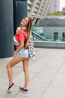 Retrato de corpo inteiro de uma jovem bem torneada com pernas longas e sapatos pretos posando de forma divertida em uma cidade