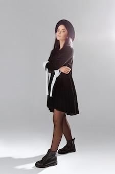 Retrato de corpo inteiro de uma jovem bonita e esguia em um vestido preto curto e chapéu posando sobre fundo branco