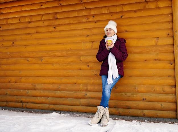 Retrato de corpo inteiro de uma jovem bonita em roupas quentes, encostada em uma parede de madeira de uma cabana de madeira e aquecendo a mão em um copo de bebida quente