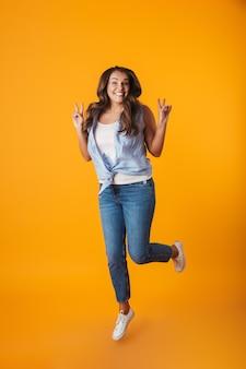 Retrato de corpo inteiro de uma jovem casual e animada, comemorando o sucesso