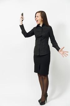Retrato de corpo inteiro de uma jovem caucasiana de cabelos castanhos com raiva, de camisa preta clássica e saia falando, gritando no celular, isolado na parede branca
