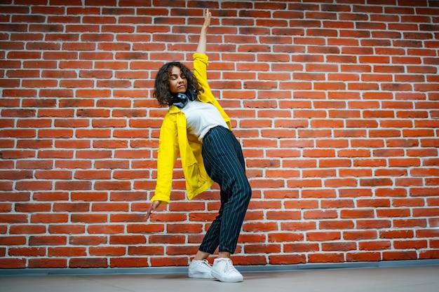 Retrato de corpo inteiro de uma jovem comemorando seu sucesso com os braços erguidos sobre o fundo de uma parede de tijolos