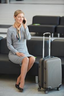 Retrato de corpo inteiro de uma jovem elegante falando por telefone e sorrindo enquanto está sentado no sofá na sala de espera do aeroporto