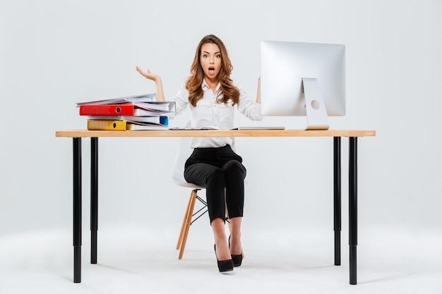 Retrato de corpo inteiro de uma jovem empresária surpresa sentada à mesa com o pc sobre fundo branco