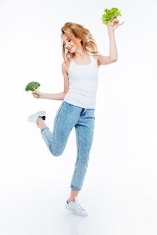 Retrato de corpo inteiro de uma jovem engraçada, couve-flor e salada verde, isolada em um fundo branco