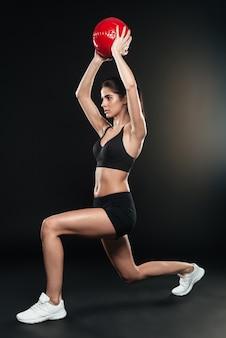 Retrato de corpo inteiro de uma jovem esportista fazendo agachamento e segurando uma bola de peso acima da cabeça, sobre a parede preta