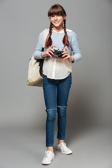 Retrato de corpo inteiro de uma jovem estudante alegre
