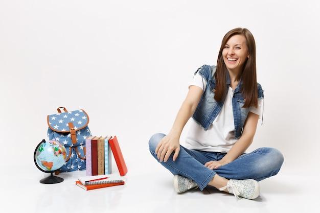 Retrato de corpo inteiro de uma jovem estudante casual rindo em roupas jeans, sentada perto de livros escolares de mochila globo isolados