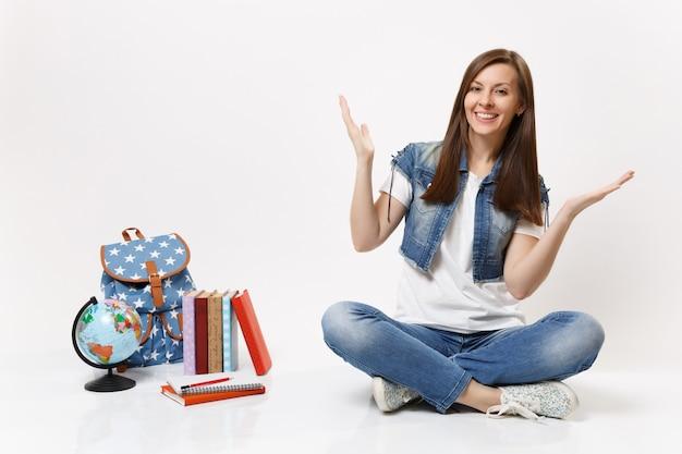 Retrato de corpo inteiro de uma jovem estudante sorridente em roupas jeans, estendendo as mãos, sentado perto da mochila de livros escolares do globo