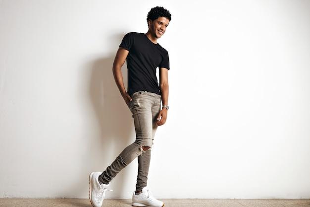 Retrato de corpo inteiro de uma jovem modelo afro-americana alta e fofa com um afro em uma camiseta de algodão preta lisa, tênis branco e jeans cinza slim isolados no branco