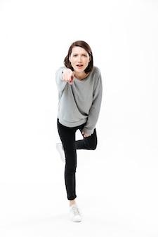 Retrato de corpo inteiro de uma jovem mulher casual, de pé em uma mão e apontando o dedo