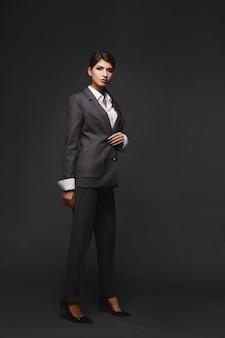 Retrato de corpo inteiro de uma jovem mulher confiante em um terno da moda no fundo cinza da moda empresarial