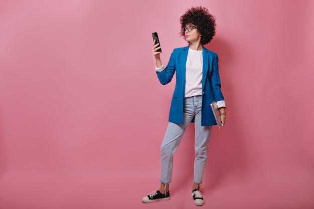 Retrato de corpo inteiro de uma jovem mulher de sucesso com um penteado curto afro em uma jaqueta azul e calça jeans usando smartphone sobre uma parede rosa