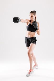 Retrato de corpo inteiro de uma jovem mulher motivada fazendo boxe