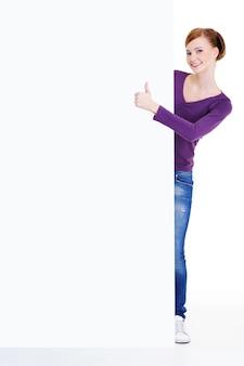 Retrato de corpo inteiro de uma jovem olhando para fora por causa de um outdoor vazio com sinal de positivo