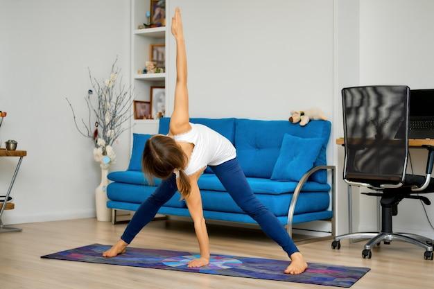 Retrato de corpo inteiro de uma jovem praticando ioga em casa, em posição de triângulo