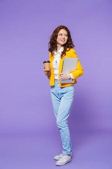 Retrato de corpo inteiro de uma jovem ruiva, muito pensativa, caminhando sobre a violeta, carregando um laptop, bebendo café