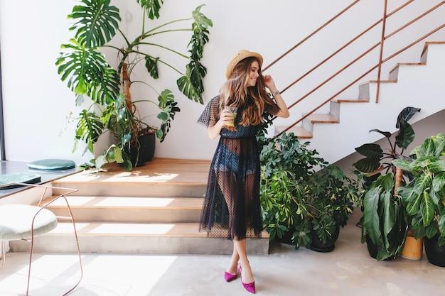 Retrato de corpo inteiro de uma jovem satisfeita com sapatos roxos em pé com um copo de suco ao lado da escada